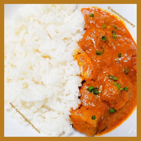 A serving of Chicken Tikka Masala with some white rice.