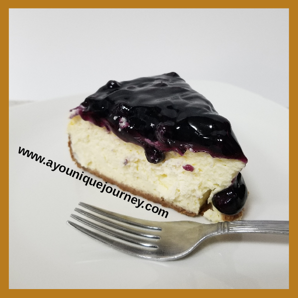 A slice of Blueberry Cheesecake on a white plate.