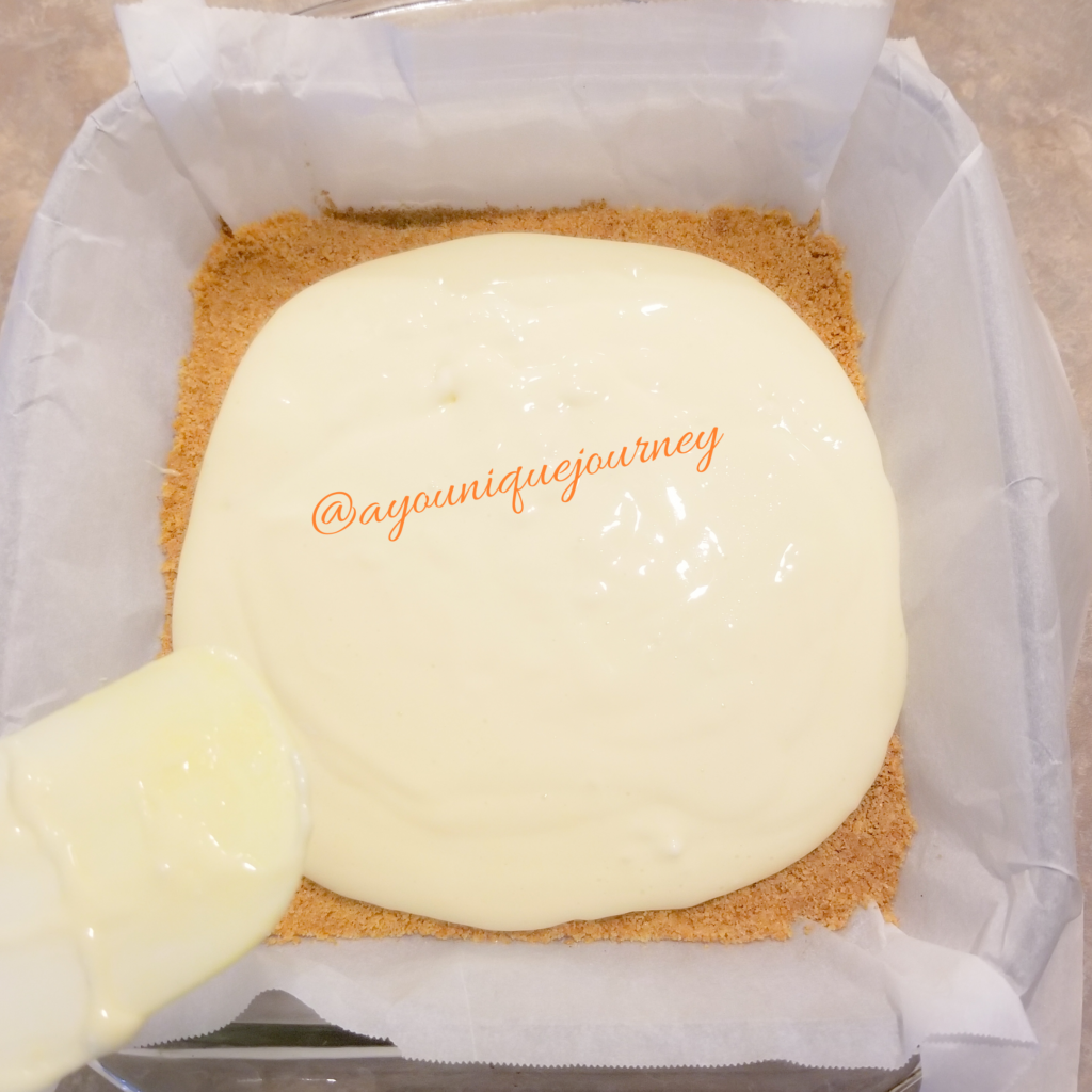 Spreading the cheesecake filling to the baked crust.