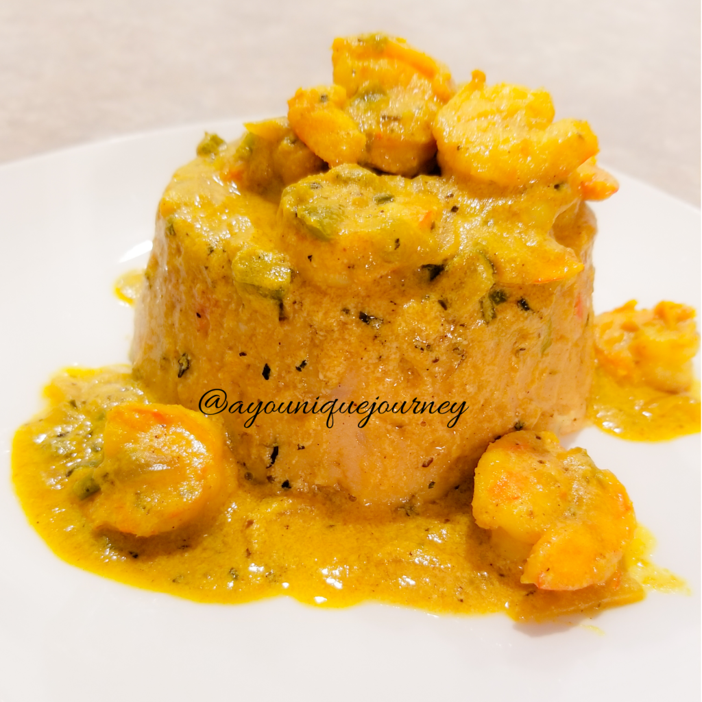 A serving of Turn Cornmeal served with Coconut Curry Shrimp.