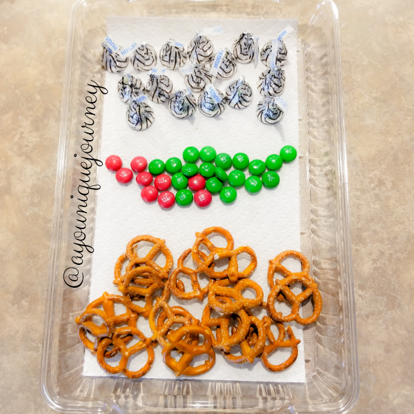 The ingredients to make Christmas Pretzel Treats: Pretzels, Green & Red M&M and Hershey's Hugs.