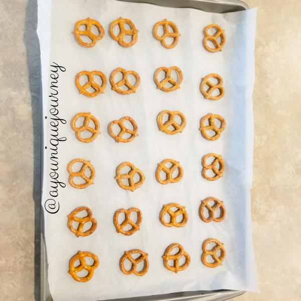 Aligning pretzels on baking sheet.