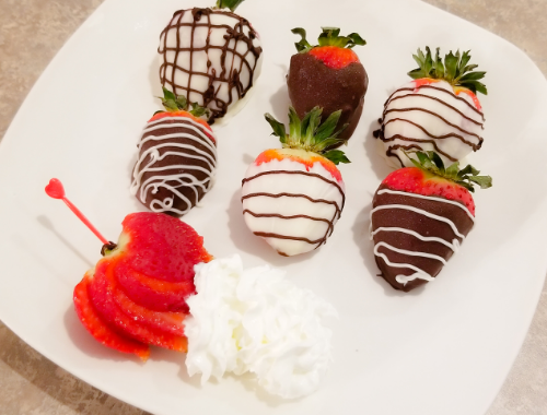 Chocolate Covered Strawberries on a white plate with some whip cream