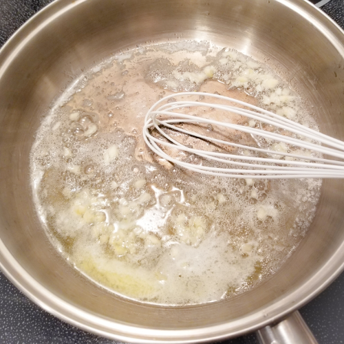 Stirring the minced garlic in the melted butter and oil.