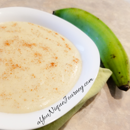 Plantain Porridge in a white bowl with a green plantain beside it.