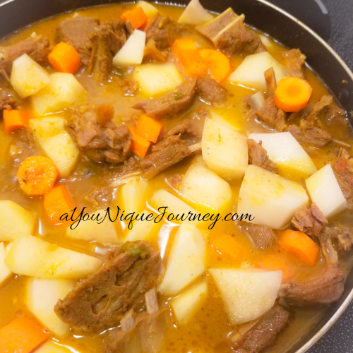 Jamaican Curry Goat with potatoes and carrots, simmering.