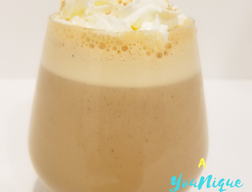 Guinness Punch Recipe in a glass with whipped cream and grated nutmeg on top.