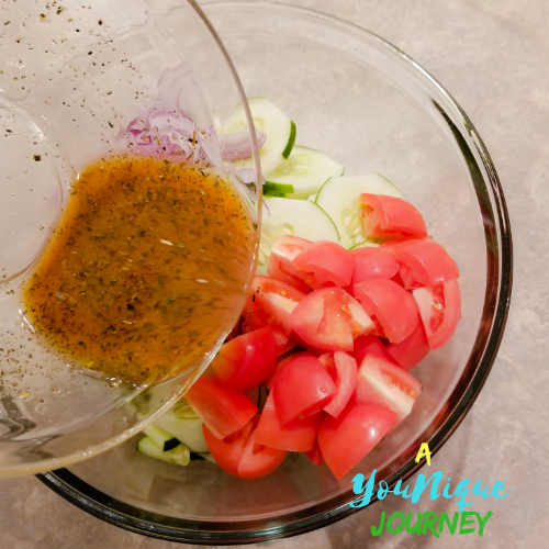 Pouring the dressing over the cucumber tomato and red onions.