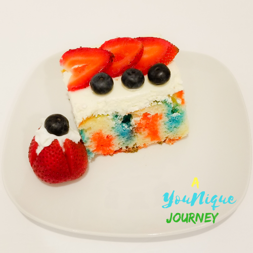 A piece of the red white and blue poke cake with a decorated strawberry with whipped cream and a blueberry on top.