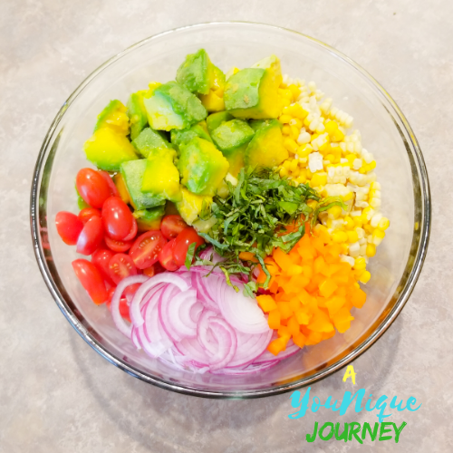 All the ingredients: corn, avocado, red onion, grape tomatoes, bell pepper and basil in a large glass bowl.