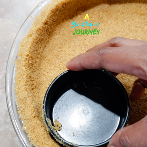 Pressing down the crust with a measuring cup into the pie dish.