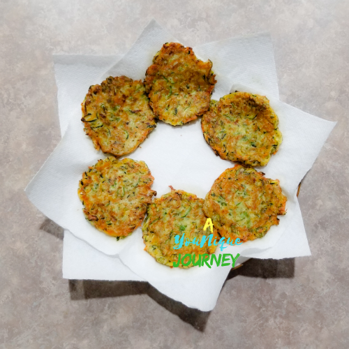 Zucchini Fritters on a plate lined with paper towel after frying.