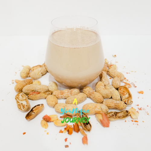 A glass of high energy Peanut Punch with peanuts around it.