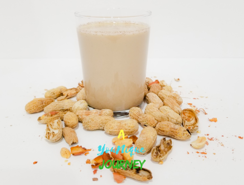 A glass of Peanut Punch with peanuts in shells around it.