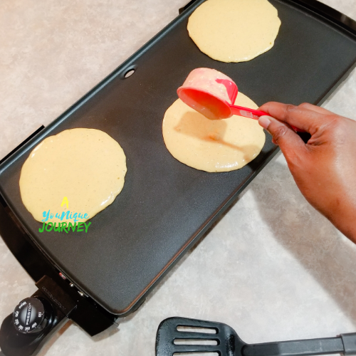 Pouring a 1/3 cup of batter on to the heated griddle.