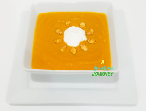 Pumpkin Soup with roasted pumpkin seeds and a dollop of sour cream on top in a white square bowl.