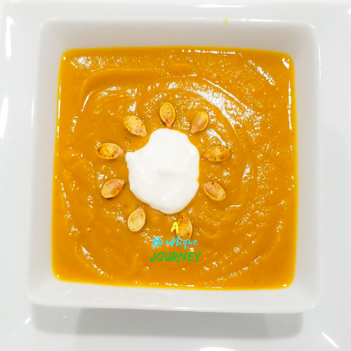 Pumpkin Soup garnished with a dollop of sour cream and roasted pumpkin seeds.