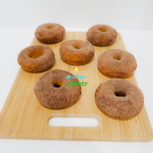 Baked Pumpkin Donuts with cinnamon sugar coating on a cutting board.