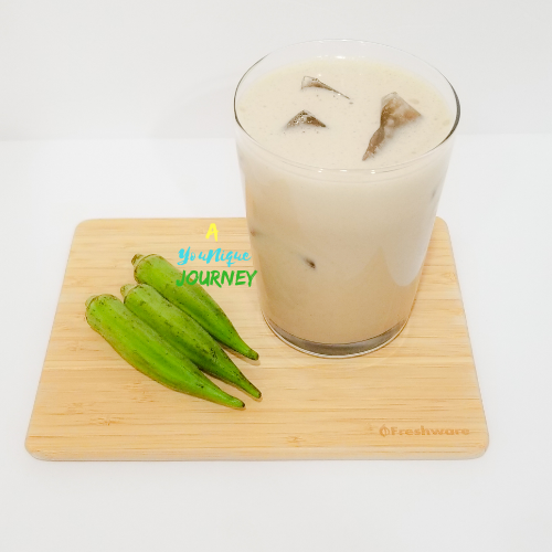 A glass of Okra Punch on a cutting board with 3 okras.