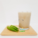 A glass of Okra Punch with 3 okras on a cutting board.