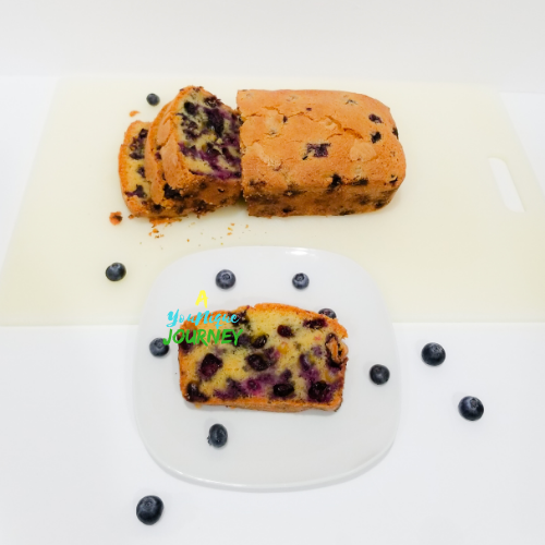 A slice of blueberry bread on a small white plate.