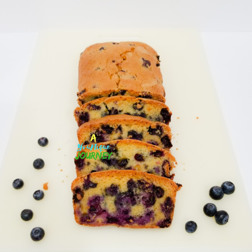 A sliced blueberry brad with blueberries at the sides.