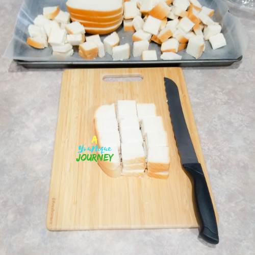 Cutting bread cubes from the hard dough bread to make eggnog bread pudding.