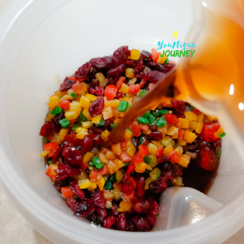 Adding the rum mixture for soaking the fruits for Jamaican Fruit Cake.