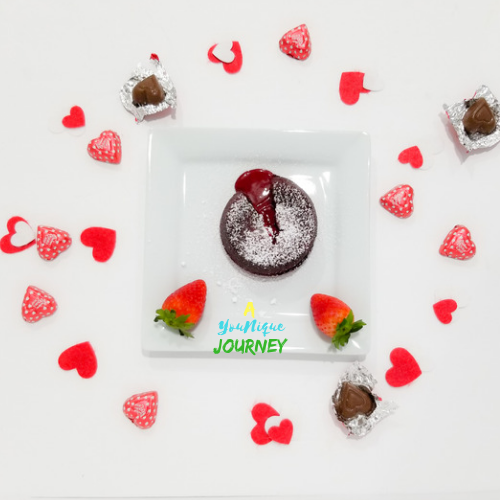 Red Velvet Lava Cake and strawberries on a serving plate with heart shaped chocolates and felt hearts.