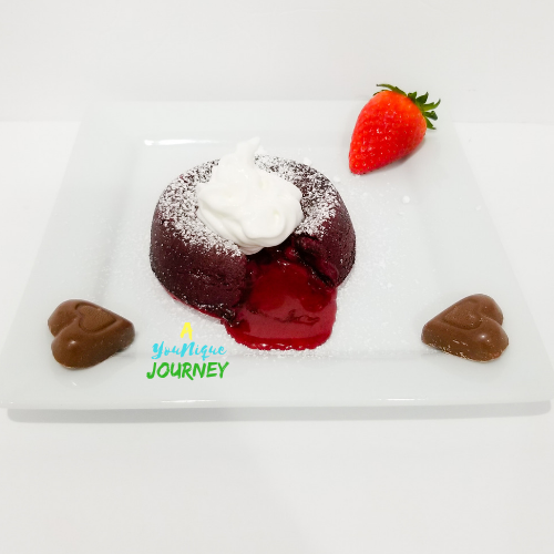 Red Velvet Molten Lava Cake on a serving plate with two heart shaped milk chocolate and a strawberry.