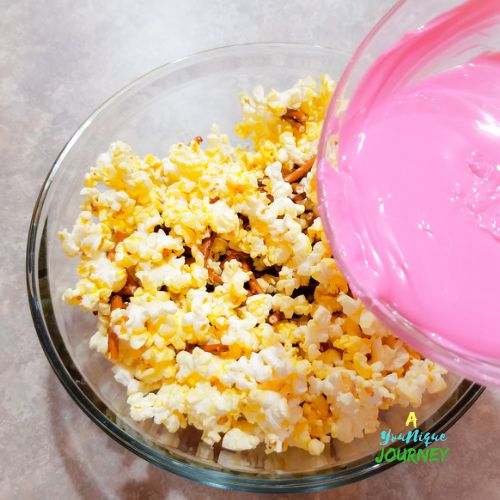 Pouring the melted candy melts wafers over the popcorn and broken pretzels.