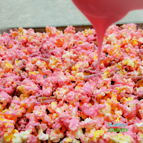 Pouring the remaining melted bright pink candy melts wafers over the coated popcorn and broken pretzels.