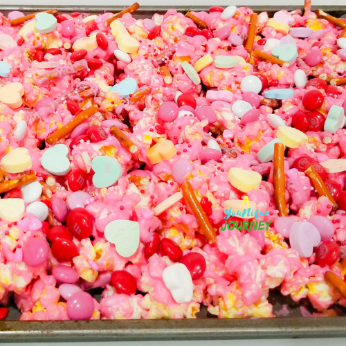 After adding the remaining broken pretzels, M&M's cupid mix, Conversation Hearts and Sprinkles to make the Valentine's Day Popcorn Mix.