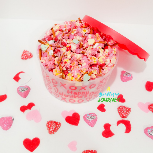 A bowl of Valentine's Day Popcorn Mix with heart shaped chocolates around it.