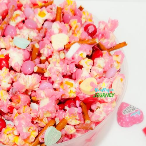 Valentine's Day Popcorn with various candies and pretzel sticks.