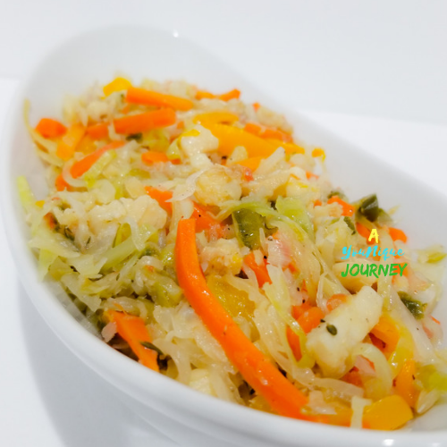Saltfish and Cabbage Recipe in a white serving bowl.
