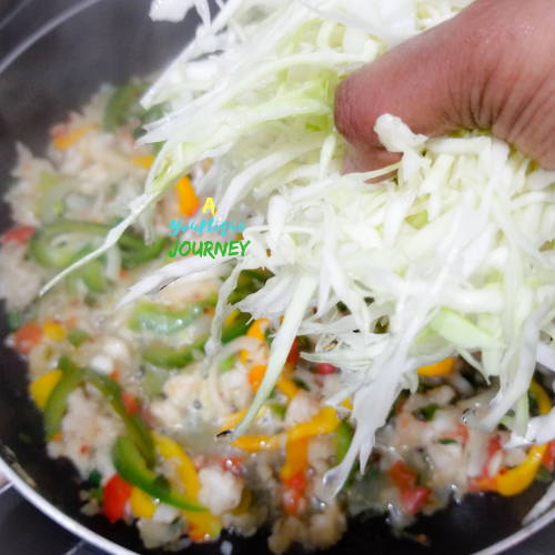 Adding the thinly sliced Cabbage to the Saltfish mixture.