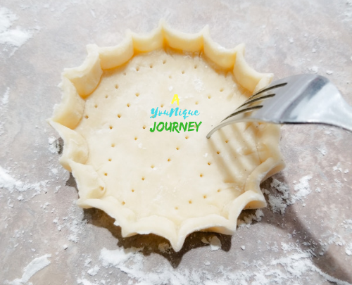 Poking the pastry shell with a fork to prevent the dough from puffy up while baking.