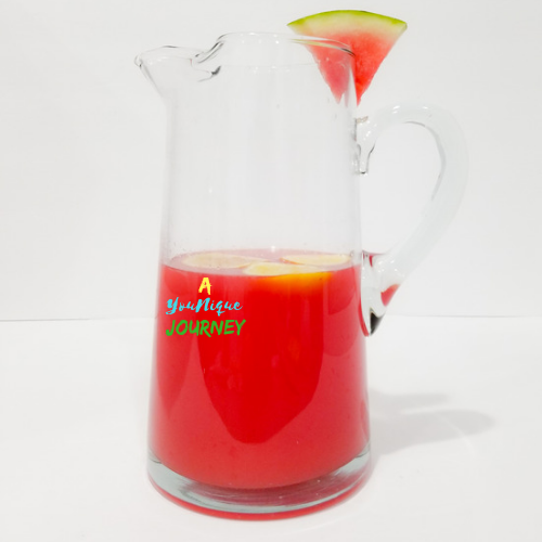 A large pitcher with watermelon and slices of lemon.