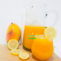Mango Lemonade in a pitcher and glass with lemon slices and a large mango.