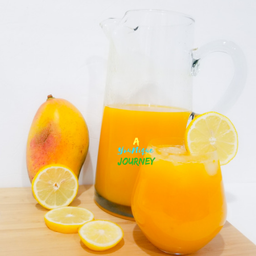 Mango Lemonade in a pitcher and a glass with lemon slices and a large mango.