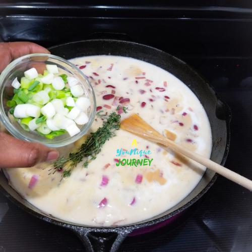 Adding the scallion (green onion) to the pot.